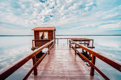 Old wooden pier for fishing, small house shed and beautiful lake. Or river in background. Picturesque natural landscape. Vacation concept royalty free stock images