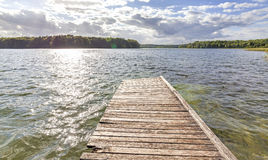 Old wooden pier at the lake with flare effect. Royalty Free Stock Photography
