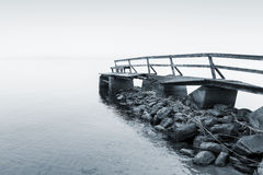 Old wooden pier on lake in foggy morning Royalty Free Stock Image