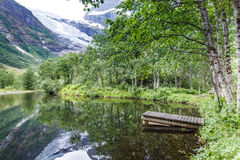 Old wooden pier on lake pond in summer. Peaceful norwegian landscape, mountains in the background Royalty Free Stock Images