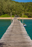 Old wooden pier leading to white sand beach Royalty Free Stock Photography