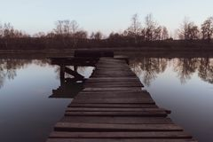 Old wooden pier at small beautiful pond on sunset. Vertical royalty free stock images
