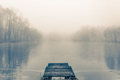 Old wooden pier. An old wooden pier on a small lake in a foggy autumn morning royalty free stock photos