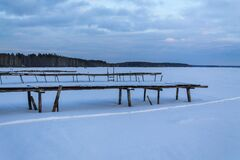Old wooden pier in the snow. Frozen lake and pine forest