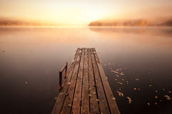 Old wooden pier on still lake with rising sun. Small wooden pier on still lake in autumnal foggy morning with rising sun Royalty Free Stock Photos