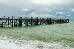Old wooden pier stretching out to sea Stock Photography
