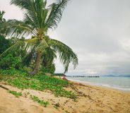 Old wooden pier stretching out to sea and foamy waves on the Maenam Beach, Koh Samui, Thailand. The Maenam Beach with coconut palms in windy cloudy weather, Koh Royalty Free Stock Photos