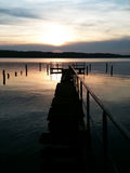 Old wooden pier at sunset. A path into an uncertain future Stock Photo
