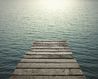 Old wooden pier to the sea with sunlight Royalty Free Stock Photography