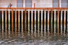 Old wooden pier wall. On water Stock Images
