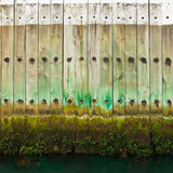 Old wooden pier wall with tidal waterline Stock Photography