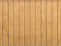 Old wooden pine boards on the wall. Old wall of wooden pine boards with knots treated yellow stain on wood Stock Photos