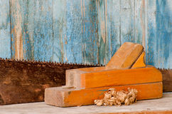 Old wooden planer and saw on vintage background, close-up Stock Images