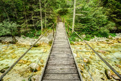 Old wooden plank bridge across beautiful river. Overcoming an obstacle concept. Stock Images