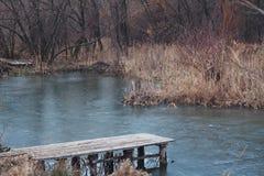Old wooden platform on frozen pond Stock Image
