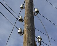 Old wooden pole. For telephone lines against the blue sky Royalty Free Stock Photo