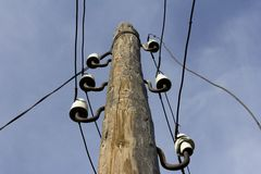 Old wooden pole. For telephone lines against the blue sky Stock Photos