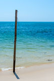 Old Wooden post stuck in white sandy beach. An Old weathered Wooden post stuck in a paradise white sand beach with a deep turquoise sea back drop Royalty Free Stock Photography