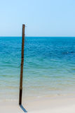 Old Wooden post stuck in white sandy beach. An Old weathered Wooden post stuck in a paradise white sand beach with a deep turquoise sea back drop Royalty Free Stock Photo