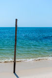 Old Wooden post stuck in white sandy beach. Royalty Free Stock Photography