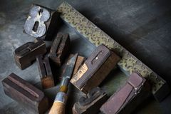 Old wooden printing press letters. A collection of old vintage wooden printing press letters and symbols, tools and decorational block stamp Stock Photos