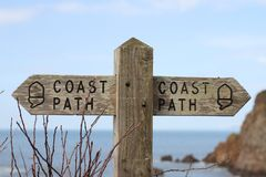 Old wooden public footpath sign overlooking Hope Cove in Devon, United Kingdom. Old wooden public footpath sign `Coast Path` overlooking Hope Cove in Devon royalty free stock images