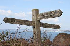 Old wooden public footpath sign overlooking Hope Cove in Devon, United Kingdom. View from across Hope Cove to Burgh Island stock photography