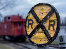 Old wooden railroad RR sign with caboose. Old fashioned wooden RR Railroad warning sign with red caboose in background in Warrenton, Virginia Royalty Free Stock Photos