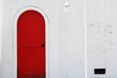Old wooden red door. In white wall Royalty Free Stock Photo