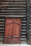 Old wooden, rickety door to the log wall. Royalty Free Stock Image