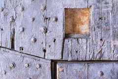 Old wooden riveted gate of fortress with a loophole Stock Photography