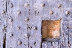 Old wooden riveted gate of fortress with a loophole Stock Images