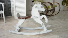 Old wooden rocking horse. On a background of an old rocking chair with a shawl stock video