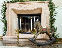 Old wooden rocking horse near the fireplace Stock Photos