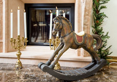 Old wooden rocking horse near the fireplace Stock Photography