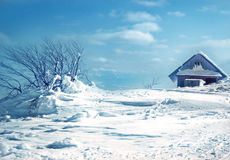The old wooden roof covered with snow and blue sky Royalty Free Stock Photography