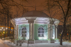 Old wooden round pavilion in winter park at night. Stock Image