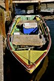 An old wooden row boat. Is docked with two sets of oars, ropes, and a cooler Stock Photo