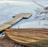 Old wooden rowboat and pier in the frozen lake Royalty Free Stock Image