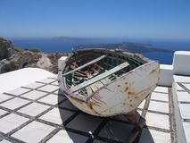 Old wooden rowing boat. On the roof of a house high above the sea on Santorini in Greece stock photo