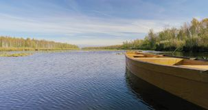 Old wooden rowing fishing boat moored near lake or river coast in beautiful autumn sunny day.  stock video footage