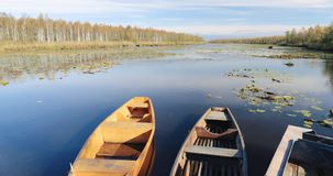 Old wooden rowing fishing boats moored near lake or river coast in beautiful autumn sunny day.  stock footage