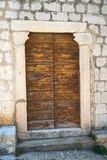 Wooden door and stone wall. Old wooden rustic door and stone wall stock photo