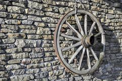 Old wooden rustic wagon wheel on a stone wall with hub and spokes. Very old wooden wheel with wood spooks and hub used on a grey stone wall Stock Images