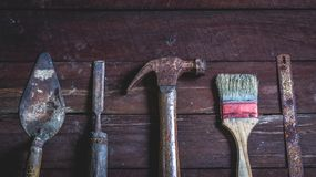 Old wooden with old rusty carpentry tools. Old wooden with rusty carpentry tools; hammer, paint brush, chisel, hacksaw, mortar. horizontal mockup stock photo