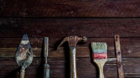 Old wooden with old rusty carpentry tools. Old wooden with rusty carpentry tools; hammer, paint brush, chisel, hacksaw, mortar. horizontal mockup royalty free stock photo