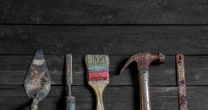 Old wooden with old rusty carpentry tools. Old wooden with rusty carpentry tools; hammer, paint brush, chisel, hacksaw, mortar. horizontal mockup stock images