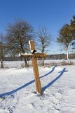 Old wooden sagging cross. Standing in the field and covered with snow in the winter season. On the surface of the cross, the paint that it was painted cracked Stock Images
