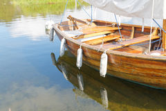 Old wooden sail boat reflecting in the water Royalty Free Stock Photo