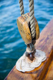 Old wooden sailboat rope attached to pulley Royalty Free Stock Photo